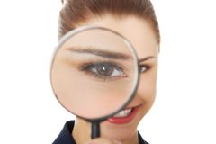 Business woman looking into a magnifying glass Stock Photo