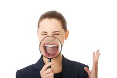 Business woman looking into a magnifying glass Royalty Free Stock Photography