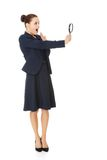Business woman looking into a magnifying glass Stock Photography