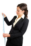 Business woman looking at a measuring tape Royalty Free Stock Photos