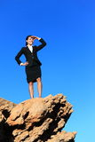 Business woman looking from mountain top. Business future concept image - businesswoman looking at horizon. Young multiracial executive Stock Photos