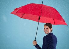 Business woman looking over shoulder with umbrella against blue background and rain Royalty Free Stock Photo