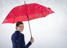 Business woman looking over shoulder with umbrella against white background and rain Royalty Free Stock Photo