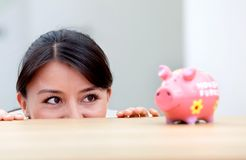 Business woman looking at a piggybank Royalty Free Stock Photos