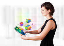 Business woman looking at tablet with pie charts. Young business woman looking at modern tablet with colourful pie charts Stock Image