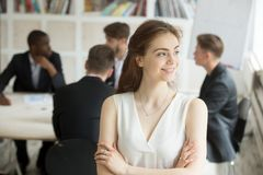 Business woman looking to side at corporate meeting. Attractive female team leader looking to side, hands crossed, colleagues discussing project ideas, results Royalty Free Stock Image