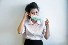 Business woman wear hygiene mask and sick. Business woman is looking to wear hygiene mask as she feels sick Royalty Free Stock Images