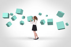 Business woman looking at turquoise cubes Royalty Free Stock Photos