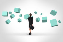 Business woman looking at turquoise cubes royalty free stock images
