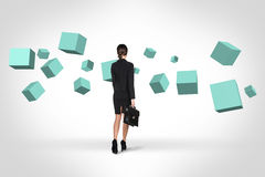 Business woman looking at turquoise cubes royalty free stock photography