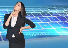Business woman looking up forefinger pressed chin Stock Photo