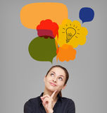 Business woman looking up on idea bulb in color bright bubble. On grey background royalty free stock image