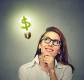 Business woman looking up at light bulb with dollar sign inside it. Happy business woman looking up at bright light bulb with dollar sign inside it stock image