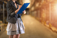 Business woman looking up order details on her clipboard. Royalty Free Stock Image