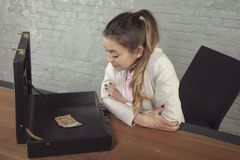 Business woman is looking at wasted money in the briefcase stock photography
