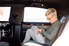 Business woman looking at watch in limousine Royalty Free Stock Image