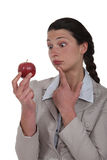 Businesswoman looking at an apple. Royalty Free Stock Image