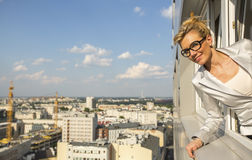 Business woman looking from the window of new high-rise buildings. Stock Photography