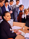 Business woman looks monitor on foreground in office. Royalty Free Stock Photo