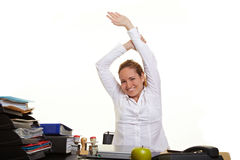 Business woman loosen up at work. Happy business woman loosen up at her desk at work Royalty Free Stock Images