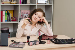 Business woman lost in thought at lunchtime. Young woman sitting at office table, laid out on the table cosmetics Royalty Free Stock Photos