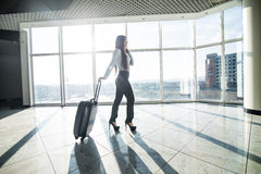 Business woman with luggage in international airport terminal waiting flight. Royalty Free Stock Photos