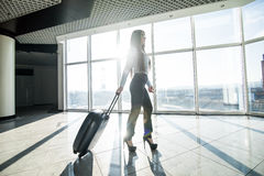 Business woman with luggage in international airport terminal waiting flight. Stock Images