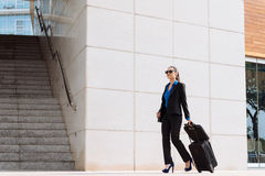 Business woman with luggage. Stylish business woman with luggage walking along the street Stock Image