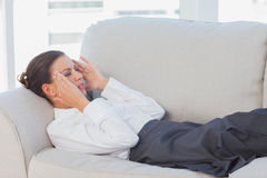 Business woman lying on couch with headache Stock Image