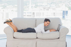Business woman lying on couch with laptop Stock Photography