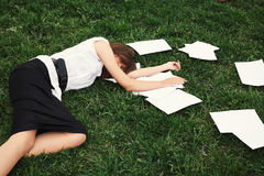 Business woman lying on grass Stock Images