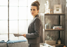 Business woman with magazine standing in loft Royalty Free Stock Image