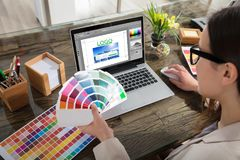 Business Woman Making Color Selection For Logo Design. A Woman Holding Color Swatches Using A Laptop With Logo Design Software On The Screen Royalty Free Stock Photos