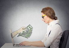 Business woman making money working on line on computer. Business woman with glasses working online on computer making earning money, hand with dollar bills Royalty Free Stock Photos