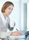 Business woman making a note while at work Royalty Free Stock Image