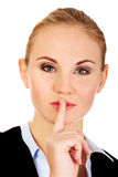 Business woman making silent sign with finger on lips Stock Photo