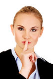 Business woman making silent sign with finger on lips Stock Photos