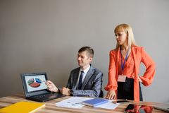 A business woman and man at a office desk  working at the projec. A business woman and man at a wooden office desk  looking at the project on the paper and stock photos