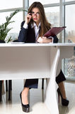 Business woman in man suit sitting at office table and looking over glasses Stock Image