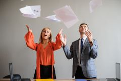 A business woman and man throwing papers up stock photos