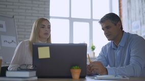 Business woman and business man working on an idea in a modern bright office 4K. Business woman and business man working on an idea in a modern bright office stock video footage