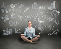 Business woman meditating on floor. Wall charts and diagrams are drawn Stock Photography