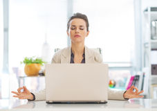 Business woman meditating near laptop Stock Photo