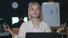 Business woman meditating in yoga pose front computer table in night office. Tired business woman meditating in yoga pose front computer table in night office stock footage