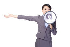 Business woman with megaphone yelling and showing. Something with open palm isolated on white background, asian model Stock Photo