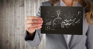 Business woman mid section with black card showing white business doodles against blurry wood panel Royalty Free Stock Photo