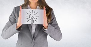 Business woman mid section with card showing grey lightbulb graphic against white wall. Digital composite of Business woman mid section with card showing grey Stock Image