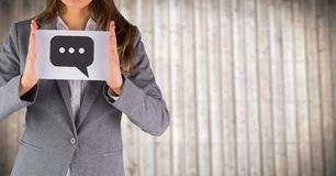 Business woman mid section with card showing speech bubble graphic against blurry wood panel Royalty Free Stock Photos