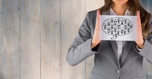 Business woman mid section with card showing speech bubble and lightbulb doodle against wood panel. Digital composite of Business woman mid section with card Royalty Free Stock Images