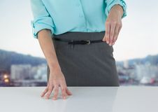 Business woman mid section at desk against blurry skyline Royalty Free Stock Images